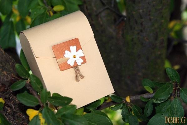 Papírová krabička se zaoblenými horními rohy a papírovou ozdobou.